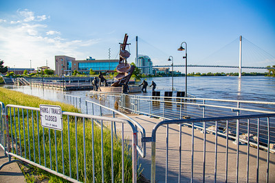 Missouri river flood of 2019, Omaha Monument to Labor, submerged in flood water, Swollen Missouri river, Bob Kerrey foot bridge, Riverfront condominiums, Carl T. Curtis, Regional headquarters National Park service, on the left, Closed Park sign, City of Omaha,