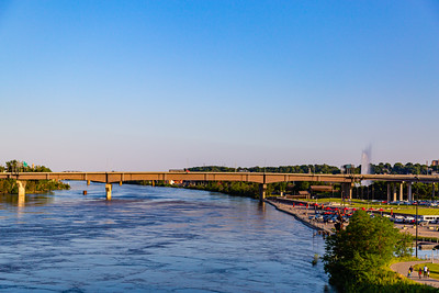 Missouri river flood of 2019 in Omaha Nebraska, swollen Missouri river under Douglas Street bridge, Heartland Park of America Fountain on the right by the bridge.
