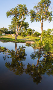 Missouri river flood of 2019 at Omaha Nebraska, Swollen Missouri River overflowing its banks and flooding the Omaha riverfront and Tom Hanafan plaza,  in Council Bluffs Iowa. Trees reflections in flood water