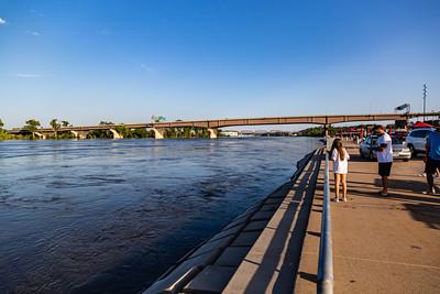 Missouri River flood of 2019. Swollen Missouri river under the Douglas Street bridge at Omaha Nebraska. Lewis and Clark landing at Omaha Riverfront  on the right.