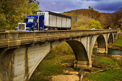 A truck crosses a bridge over the Current River in the southern Missouri Ozarks. Crane Lake at sunrise on a cloudy morning.   Photo by Kyle Spradley | www.kspradleyphoto.com