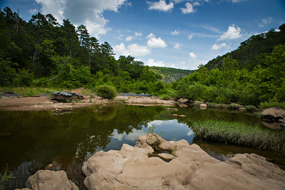 Float along the St. Francis River in Madison County, Missouri in summer. This lesser-known stretch of the famed river is loaded with boulders and scenic bluffs. Lee's Bluff and the Fish Trap and two prominent points along the way. The caverns at Marsh Creek also are a scenic geologic feature along the river.  Photo by Kyle Spradley | © Kyle Spradley Photography | www.kspradleyphoto.com