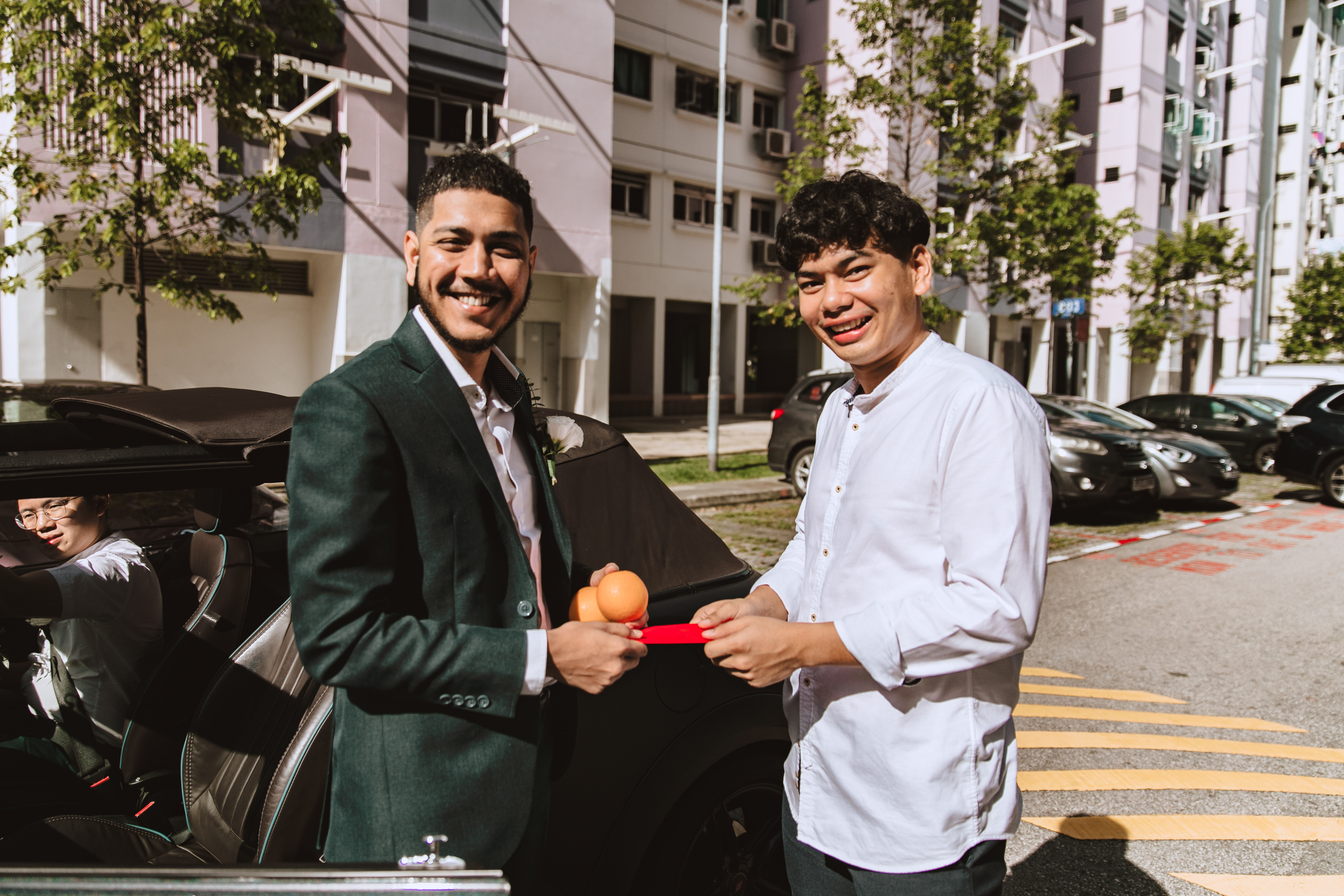 Groom receiving mandarin oranges from bride's younger brother
