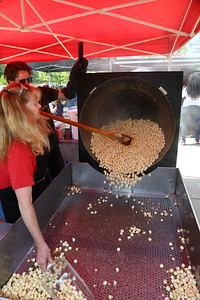 George P. Smith/The Montgomery Sentinel    Robin Evans looks on as Aaron Gage tips the kettle with Fresh-popped Kettle Corn Sweet & Salty at the Fifth Annual Montgomery County GreenFest held jointly with Brookside Gardens' Earth Day Celebration on Sunday, April 28, 2019 at Brookside Gardens in Wheaton.