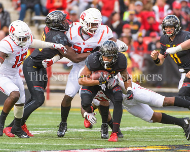 Terps sophomore running back Ty Johnson of Cumberland, MD takes advantage of a opening in the line while dragging a Scarlet Knight with him.
