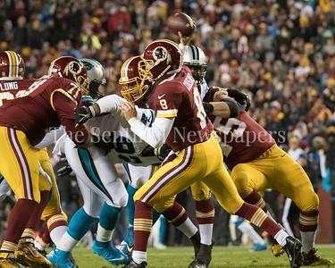 Kirk Cousins gets hit as he unloads a pass.
