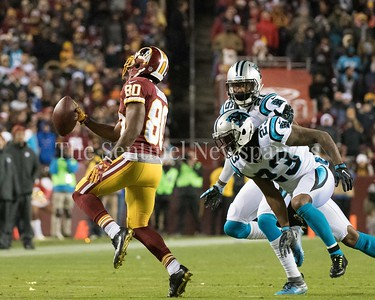 Jamison Crowder runs for the sidelines and a first down  as the Panther's defense closes in.