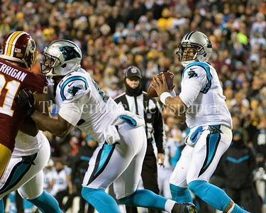 Kerrigan gets tied up at the line giving Cam Newton time to unload a long pass.