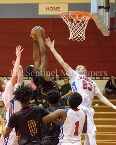 Bladensburg's Oladapo reels in a rebound surrounded by Sherwood players.