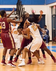 In another battle for posession of the ball in the lane, Gaithersburg's Jeweles Pritchett (23) puts some muscle into the mixup.