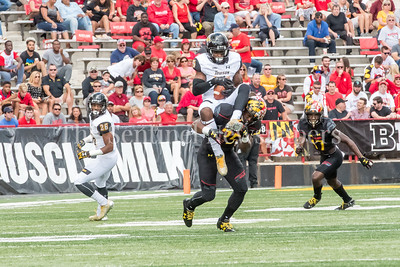 9/9/2017 - Trey Kilgore (15) holds on to the ball as he's tackled by Antoine Brooks (25), Towson v University of Maryland Football, Photo Credit: Jacqui South