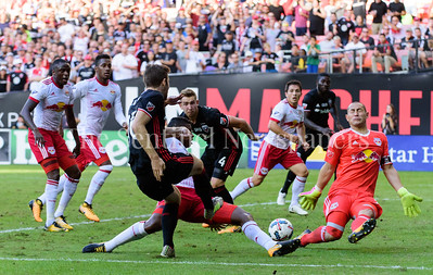 Patrick Mullins, a forward for DC United unloads a rocket that was deflected at the last moment by Red Bull defender Kemar Lawrence who got injured on the play.  Red Bull keeper Luis Robles tensed up ready to stop the shot with his eyes closed.   DC United vs NY Red Bulls  10-22-17 Photo by David Wolfe