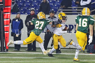 George P. Smith/The Montgomery Sentinel    Damascus High School's Ben Lokos (#27) reaches out for Gwynn Park High School's Kibwe Galloway (#4) and gets a hold of his jersey to shut down this run in the State 2A Final game played at Navy-Marine Corps Memorial Stadium in Annapolis on Saturday, December 2, 2017.