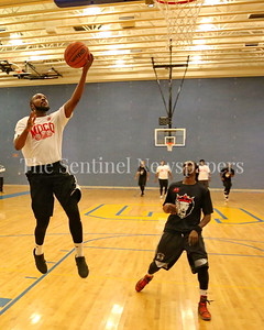 George P. Smith/The Montgomery Sentinel    MoCo Big III Select's Jeremy Williams (#4) taking it to the hoop past Victor's Dele Ojo (#3).