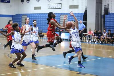 "George P. Smith/The Montgomery Sentinel    Wheaton High School's Crystal Jones (#13) drives the lane past James Hubert ""Eubie"" Blake High School's Alexandra Konzmann (#11)."