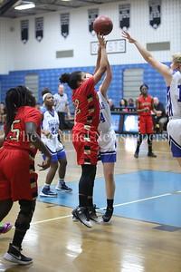 "George P. Smith/The Montgomery Sentinel    Wheaton High School's Teefa Alli (#12) shoots as James Hubert ""Eubie"" Blake High School's Lauren McGinn (#24) and Alexandra Konzmann (#11) try to block."