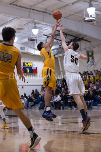 Miles English of B-CC reaches over Bullis' CJ Amsellem for 2 of his 16 points. PHOTO BY MIKE CLARK