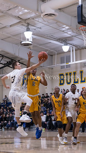 Lincoln Yeutter of Bullis drives in for the under-handed layup against Justin Graves. PHOTO BY MIKE CLARK