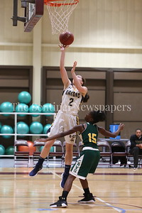 George P. Smith/The Montgomery Sentinel    Bethesda-Chevy Chase High School's Caroline Orza (#2) makes the layup over John F. Kennedy High School's Tamia Howard (#15) off the assist from Caitlyn Clendenin (#21) in the CKA SAVE Project 2017 Holiday Tournament Final played at Howard Community College Wednesday December 27, 2017.