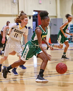 George P. Smith/The Montgomery Sentinel    John F. Kennedy High School's Tamia Howard (#15) drives up court with Bethesda-Chevy Chase High School's Charlotte Lowndes (#11) in pursuit in the CKA SAVE Project 2017 Holiday Tournament Final played at Howard Community College Wednesday December 27, 2017.