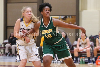 George P. Smith/The Montgomery Sentinel    Bethesda-Chevy Chase High School's Stephanie Howell (#14) battles John F. Kennedy High School's Asia Lewis (#10) under the boards in the CKA SAVE Project 2017 Holiday Tournament Final played at Howard Community College Wednesday December 27, 2017.