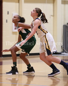 George P. Smith/The Montgomery Sentinel    Bethesda-Chevy Chase High School's Caroline Orza (#2) battles John F. Kennedy high School's Kaylynn Bromell (#22) for position under the boards in the CKA SAVE Project 2017 Holiday Tournament Final played at Howard Community College Wednesday December 27, 2017.