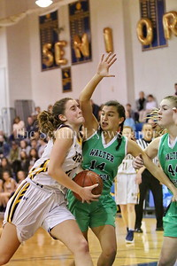 George P. Smith/The Montgomery Sentinel    Bethesda-Chevy Chase High School's Caitlyn Clendenin (#21) drives the lane and gets mauled by Walter Johnson High School's Sonia Tavik (#14) and Madison Kemp (#44).