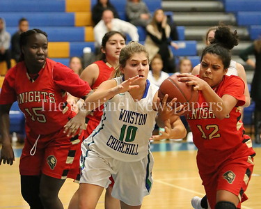 George P. Smith/The Montgomery Sentinel    Wheaton High School's Teefa Alli (#12) and Winston Churchill High School's Leah Rubino (#10) go after a loose ball during the game played at Churchill on Tuesday, January 2, 2018.
