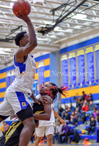 Tao Huka of Gaithersburg plows over Daryn Alexander of Richard Montgomery to add 2 points.  Gaithersburg vs Richard Montgomery Boys Varsity Basketball Photo Credit:  David Wolfe