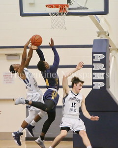 George P. Smith/The Montgomery Sentinel    Georgetown Preparatory School's Miles Somerville (#2) gets a hand on the ball as Bullis' Nendah Tarke (#4) goes up for a layup and takes out Prep's William Mulquin (#15)  in the game played Thursday, January 11, 2018 at Prep.
