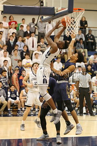 George P. Smith/The Montgomery Sentinel    Bullis' Phillip Smith with the hand in back as  Georgetown Preparatory School's Ike Nwebe (#24) puts back a rebound in the game played Thursday, January 11, 2018 at Prep.