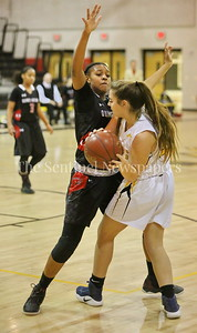 George P. Smith/The Montgomery Sentinel    Quince Orchard High School's Destini Kelly (#14) presses and traps Richard Montgomery High School's Chloe Sherman (#23) in the game played Friday, January 19, 2018.