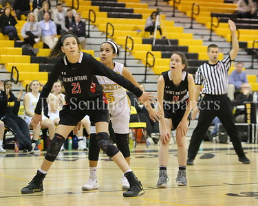George P. Smith/The Montgomery Sentinel    Quince Orchard High School's Tatiana Popa (#21) boxes out Richard Montgomery High School's Ellie Tounkara (#5) as Maggie Regan (#11) holds her spot in the game played Friday, January 19, 2018.