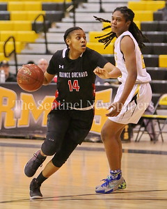 George P. Smith/The Montgomery Sentinel    Quince Orchard High School's Destini Kelly (#14) drives the lane past Richard Montgomery High School's Nusaibah Rashad (#24) in the game played Friday, January 19, 2018.