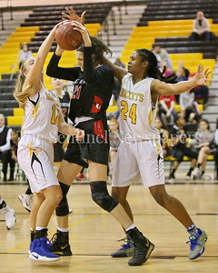 George P. Smith/The Montgomery Sentinel    Quince Orchard High School's Tatiana Popa (#21) gets shut down by Richard Montgomery High School's Melanie Osborne (#12) and Nusaibah Rashad (#24) in the game played Friday, January 19, 2018.