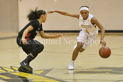 George P. Smith/The Montgomery Sentinel    Richard Montgomery High School's Karon Williams (#4) puts a move on Quince Orchard High School's Anaya Badmus (#3) in the game played Friday, January 19, 2018.