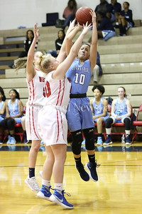 George P. Smith/The Montgomery Sentinel    Clarksburg High School's Miki Howson (#10) gets a shot off over  Wootton's Mary Quackenbush (#50) and Zoey Goldberg (#5) in the game played on the Patriot's home court on January 29, 2018.