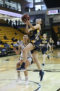 George P. Smith/The Montgomery Sentinel    Bethesda-Chevy Chase High School's Caitlyn Clendenin (#21) scored a layup, for 2 of her 22 team-high points, in a loosing effort that saw the Barons fall to Catonsville High School 63-51 in the State semifinal game played at at Towson University on March 8, 2018.