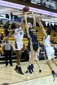 George P. Smith/The Montgomery Sentinel   Catonsville High School's Jasmine Dickey (#20) swats the ball as Bethesda-Chevy Chase High School's Caitlyn Clendenin (#21) shoots and Jameila Barrett (#1) comes over to help block.