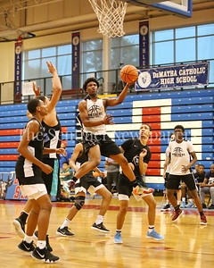 George P. Smith/The Montgomery Sentinel    Paint Branch High School's  Richard Dudley (5) splits the Eleanor Roosevelt High School defense to make this layup during the Capitol Hoops Summer League game  played at DeMatha High School on Sunday, June 3, 2018.