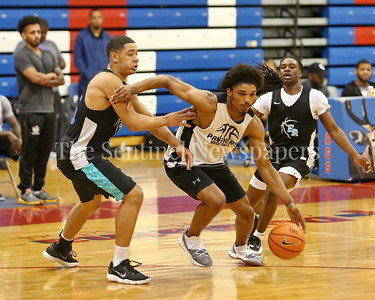 George P. Smith/The Montgomery Sentinel    Paint Branch High School's Jordan Alphonso (20) driving the lane past Eleanor Roosevelt High School's Isaiah Gross (25) during the Capitol Hoops Summer League game  played at DeMatha High School on Sunday, June 3, 2018.