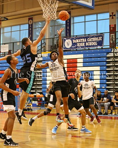George P. Smith/The Montgomery Sentinel    Eleanor Roosevelt High School's Isaiah Gross (25) tries to block the layup by Paint Branch High School's Jordan Alphonso (20) during the Capitol Hoops Summer League game  played at DeMatha High School on Sunday, June 3, 2018.