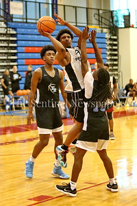 George P. Smith/The Montgomery Sentinel    Paint Branch High School's  Richard Dudley (5) takes a shot over the outstretched hands of Eleanor Roosevelt High School's Olumide Lewis (10) during the Capitol Hoops Summer League game  played at DeMatha High School on Sunday, June 3, 2018.