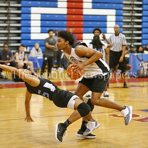 George P. Smith/The Montgomery Sentinel    Eleanor Roosevelt High School's Jahari Simon (15) takes a charge from Paint Branch High School's Jordan Alfonso (20) during the Capitol Hoops Summer League game  played at DeMatha High School on Sunday, June 3, 2018.