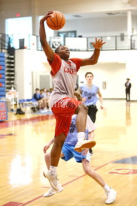 George P. Smith/The Montgomery Sentinel    St. John's College High School's Saveon Jackson (12) with a layup past Walt Whitman High School's Sean Farren (12) during the Capitol Hoops Summer League game  played at DeMatha High School on Sunday, June 3, 2018.