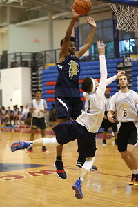George P. Smith/The Montgomery Sentinel    Bullis School's Cole Hanin (11) shoots as he is falling while Counsel's Phillip Carter (5) tries to block during the Capitol Hoops Summer League game played Saturday, June 9, 2018 at DeMatha Catholic High School.