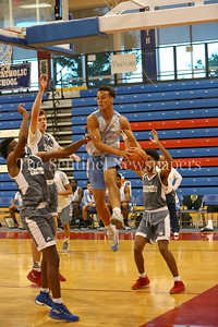 George P. Smith/The Montgomery Sentinel    Springbrook High School's Justin Cook (21) runs into traffic and ditches the ball across the key during the Capitol Hoops Summer League game played at DeMatha High School Friday, June 15, 2018.