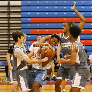 George P. Smith/The Montgomery Sentinel    Springrook High School's Jonathan Lapierre (23) gets trapped as he drives to the basket during the Capitol Hoops Summer League game played at DeMatha High School Friday, June 15, 2018.