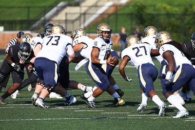 George P. Smith/The Montgomery Sentinel    Our Lady of Good Counsel High School quarterback Kamerun Snell (16) handing off to Sean Aaron (27) in the game against Northwest High School played at Gaithersburg High School on Saturday, September 29, 2018 due to wet field conditions at Northwest.