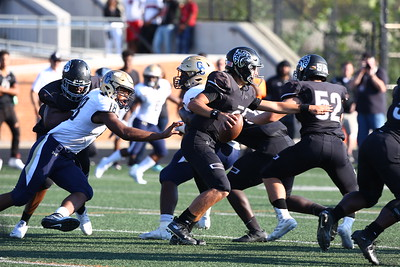 George P. Smith/The Montgomery Sentinel    Northwest High School quarterback Jack Anders (8) under pressure from Our Lady of Good Counsel High School's Kristopher Jenkins (18) in the game played at Gaithersburg High School on Saturday, September 29, 2018 due to wet field conditions at Northwest.